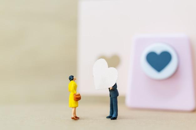 Miniaturleute: paare mit papierherzen auf hölzernem hintergrund