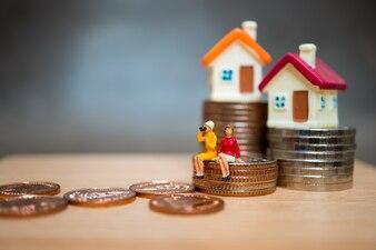Miniaturleute, Paarfrau, die auf Stapelmünzen und Minihaus sitzt