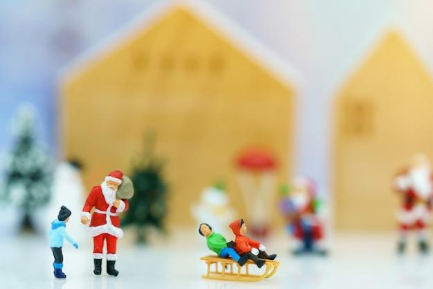 Miniaturleute: santa claus mit den kindern, die spaß mit schnee und weihnachtsbaum spielen.