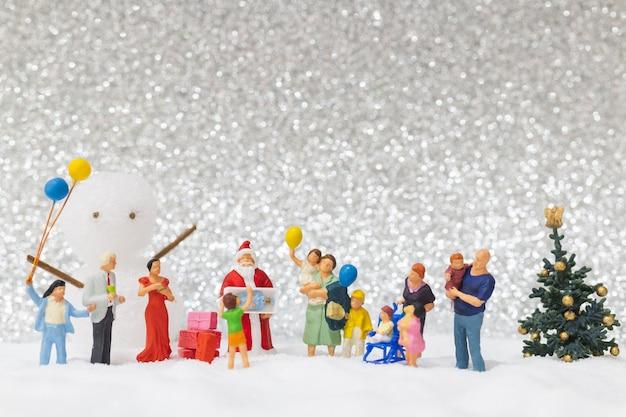 Miniaturleute: santa claus und kinder mit schneehintergrund