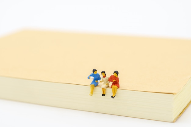 Miniaturleute sitzen auf notizbuch. geschäftskonzept und teamwork-konzept