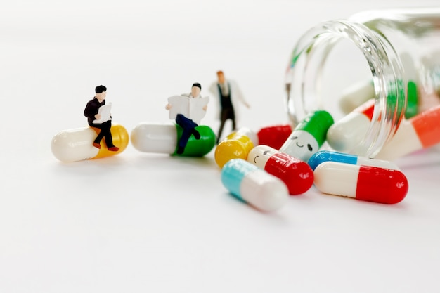 Miniaturleute sitzen und lesen mit ärzten ein buch über medizin.