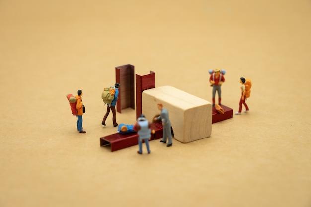 Miniaturleute stehen auf gehen sie durch den scanner, bevor sie das flughafentor betreten.