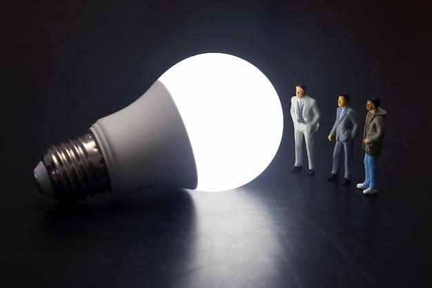 Miniaturleute stehen in der nähe einer led-glühbirne
