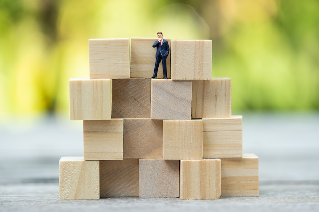 Miniaturleute: überzeugte geschäftsleute auf puzzlenikone, erfolg, handel, gruß und partnerkonzept.