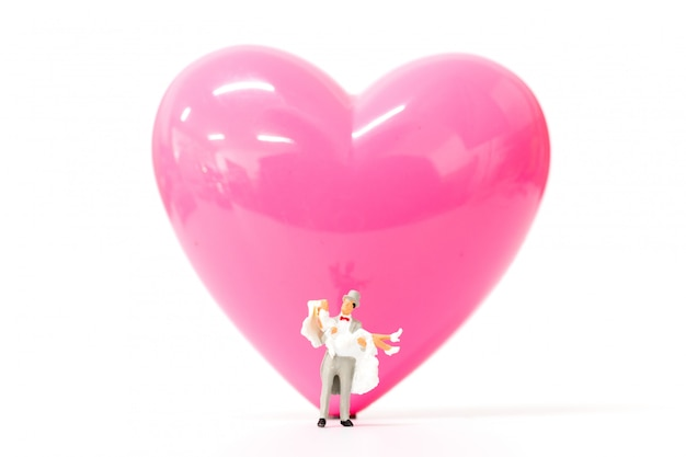 Miniaturleute verbinden mit rosa herzen auf weißem hintergrund