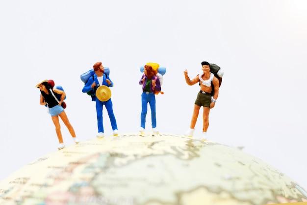 Miniaturleute, wanderer auf dem globus, der zum bestimmungsort geht.