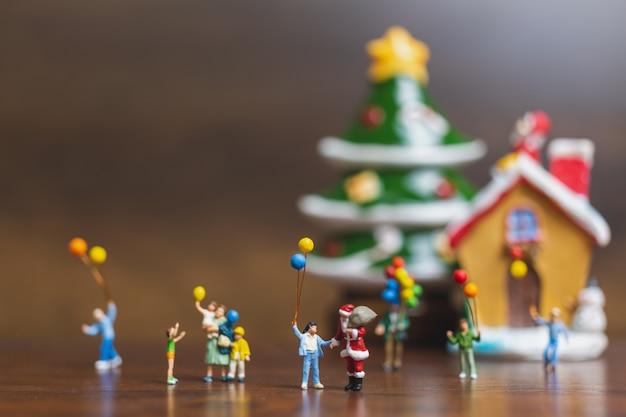 Miniaturleute: weihnachtsmann und kinder, die ballon halten