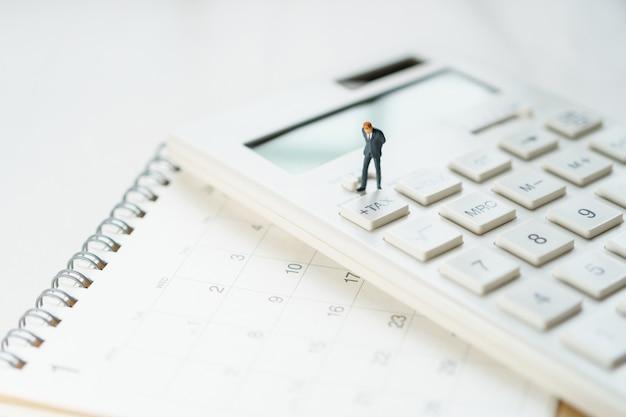Miniaturleute zahlen warteschlange jährliches einkommen (tax) für das jahr auf dem taschenrechner.