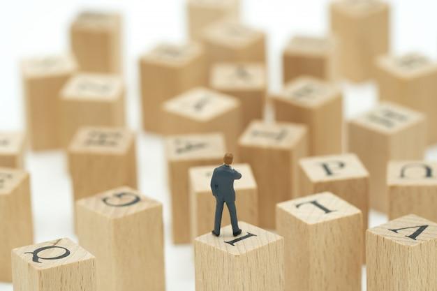 Miniaturleutegeschäftsmänner analysieren die stellung auf hölzernen wörtern