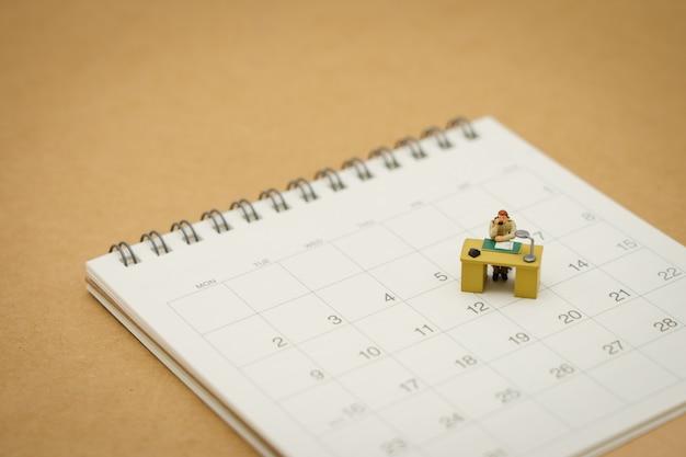 Miniaturleutegeschäftsmänner auf weißem kalender verwenden als hintergrundgeschäftskonzept