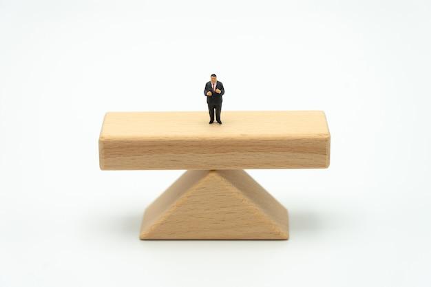 Miniaturleutegeschäftsmänner, die auf den holzbalken stehen, die auf beiden seiten stehen