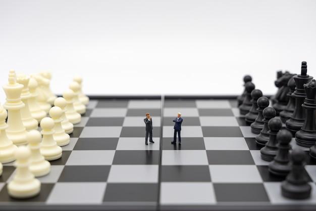 Miniaturleutegeschäftsmänner, die auf einem schachbrett mit einer schachfigur stehen