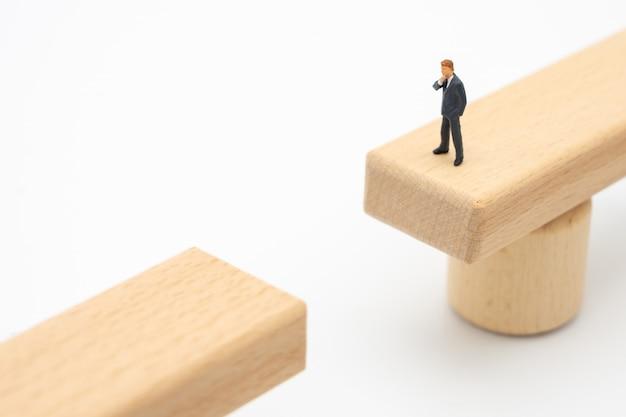 Miniaturleutegeschäftsmänner, die auf einer holzbrücke schauen stehen
