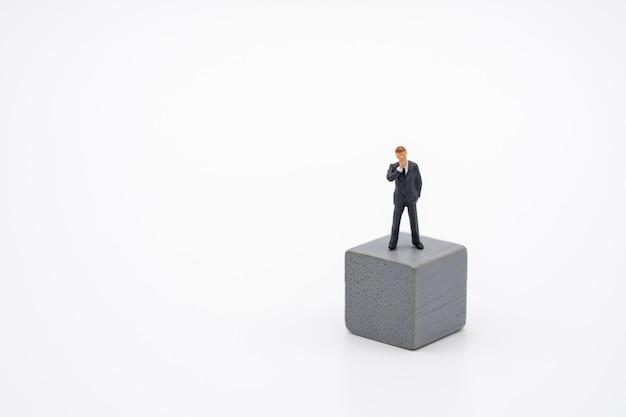Miniaturleutegeschäftsmänner, die auf hölzernem würfel investmentanalyse stehen