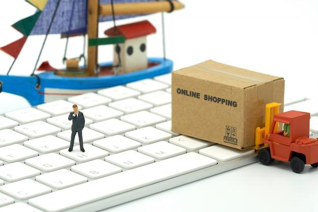 Miniaturleutegeschäftsmänner, die auf on-line-einkaufskonzept der tastatur stehen