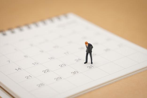 Miniaturleutegeschäftsmänner, die auf weißem kalender stehen