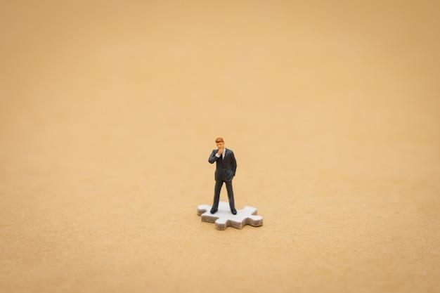 Miniaturleutegeschäftsmänner, die auf weißer laubsäge stehen. als hintergrund verwenden