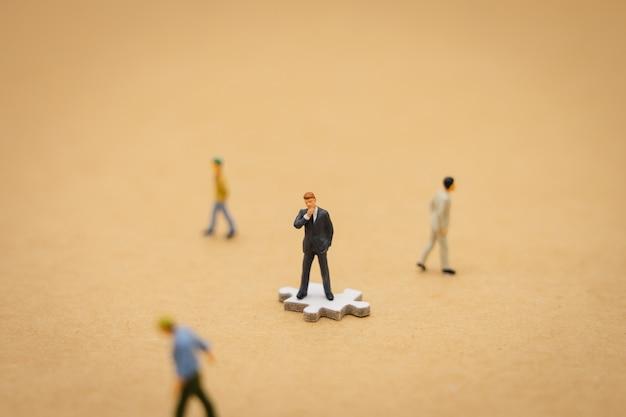 Miniaturleutegeschäftsmänner, die auf weißer laubsäge stehen. das bei der auswahl verwendete konzept