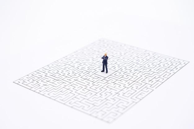 Miniaturleutegeschäftsmänner, die in der mitte des labyrinths stehen. geschäftsidee