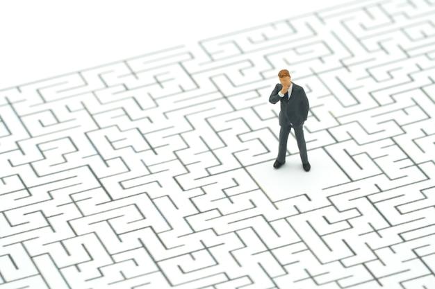 Miniaturleutegeschäftsmänner, die in der mitte des labyrinths stehen.