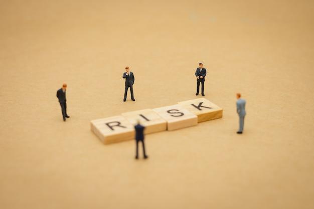 Miniaturleutegeschäftsmänner, die mit hölzernem wort risiko stehen