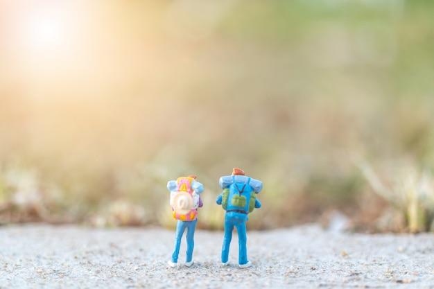 Miniaturleutekonzept mit reisenden miniatur mit dem rucksack, der auf der straße steht