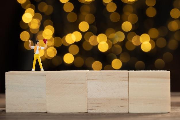 Miniaturmann auf kubischem holz, das rotes herz für liebhaber mit gelben lichtern hält