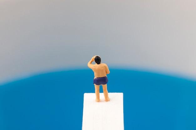 Miniaturmann, der auf sprungbrett steht