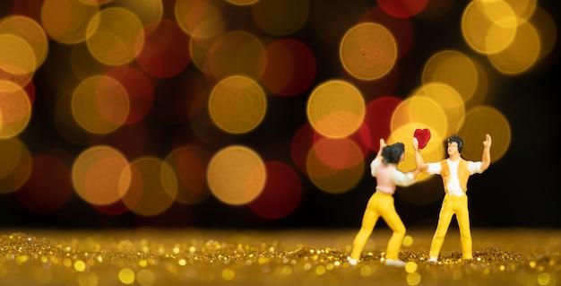Miniaturmann, der rotes herz für liebhaber mit lichtern hält