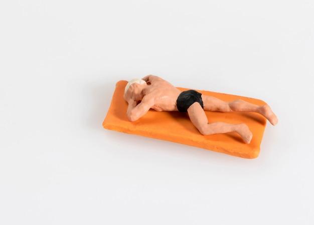 Miniaturmann in liegendem ein sonnenbad nehmen des schwimmenkostüms