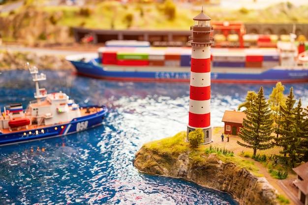 Miniaturmeer mit schiffen und einem leuchtturm am ufer