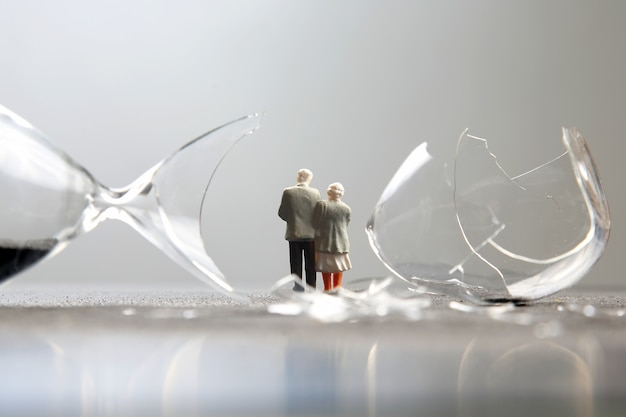 Miniaturmenschen. ältere menschen gehen in der nähe der kaputten sanduhr. verlust der lebenszeit. hoffnungskrise und altersprobleme
