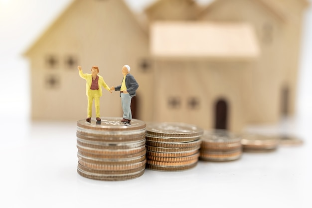 Miniaturmenschen: ältere person, die auf münzenstapel mit haus steht, vorsorgeplanungskonzept.