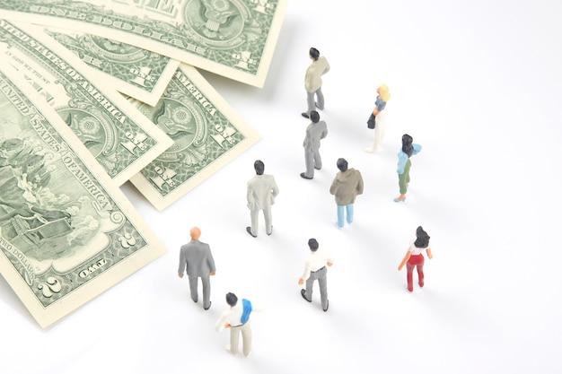 Miniaturmenschen. anderer geschäftsmann steht in der nähe von dollargeld. investitionen und einkommen für die arbeit