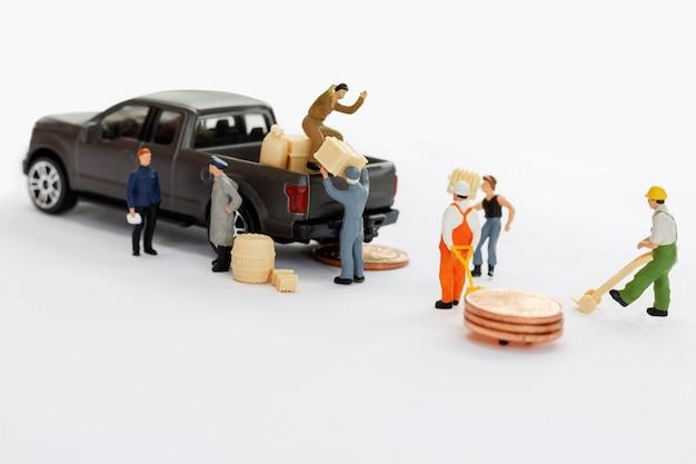 Miniaturmenschen: arbeiter bewegen münzstapel zum kleintransporter.