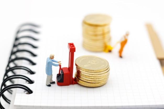 Miniaturmenschen: arbeiter transportieren münzengeld auf buch.