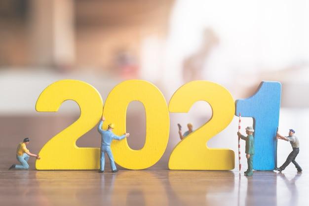 Miniaturmenschen: arbeiterteam bauen holznummer 2021, frohes neues jahr-konzept