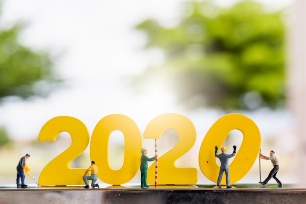 Miniaturmenschen: arbeiterteam baut holz nr. 2020