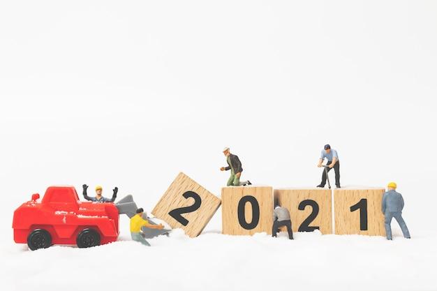 Miniaturmenschen: arbeiterteam erstellen holzblocknummer 2021, frohes neues jahr-konzept