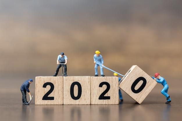 Miniaturmenschen: arbeiterteam schafft holzblock nummer 2020