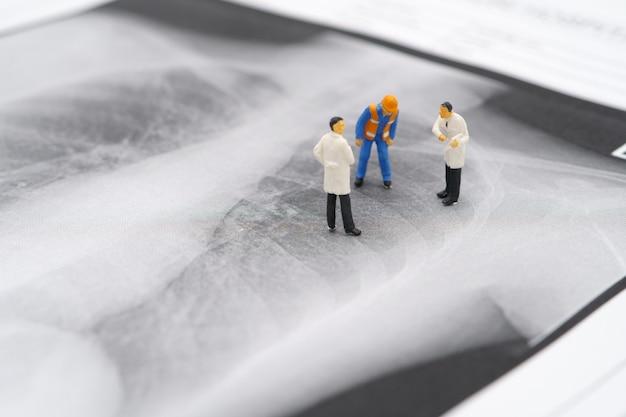 Miniaturmenschen arzt und bauarbeiter auf lungenröntgen um nach covid 19-viren oder coronaviren zu suchen