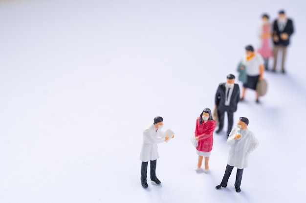 Miniaturmenschen: arzt und patient auf weißem hintergrund, gesundheitskonzept.