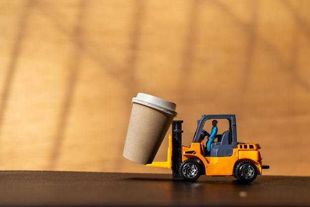 Miniaturmenschen auf gabelstapler und kaffee zum mitnehmen