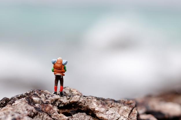 Miniaturmenschen: backpacker, der erfolg feiert, der oben auf einem berggipfel steht.