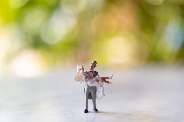 Miniaturmenschen: braut und bräutigam im freien mit grünem bokeh-hintergrund und kopierraum für text