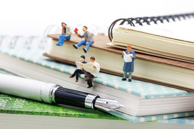Miniaturmenschen: business-team liest buch, ausbildung oder geschäftskonzept.