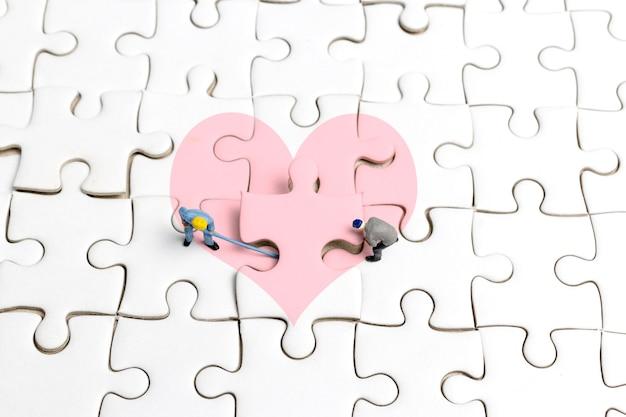 Miniaturmenschen das team arbeitet an einem puzzleteil mit herzform.