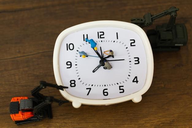 Miniaturmenschen: das team arbeitet an einem wecker