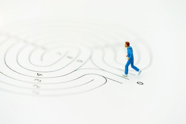 Miniaturmenschen, die am startpunkt des labyrinths laufen und darüber nachdenken, wie dieses problem gelöst werden kann.